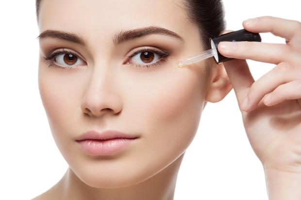 Girl applying eye serum