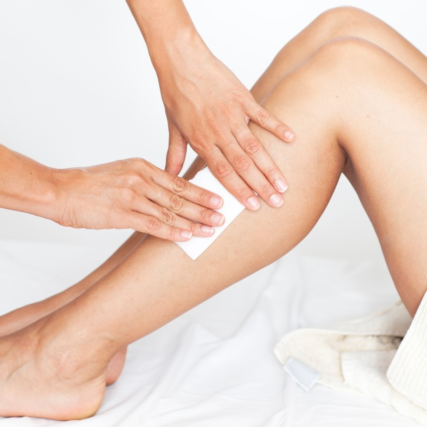 Removing hair from womans legs in a beauty spa during a beauty treatment